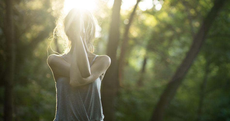 森で日光を浴びている女性