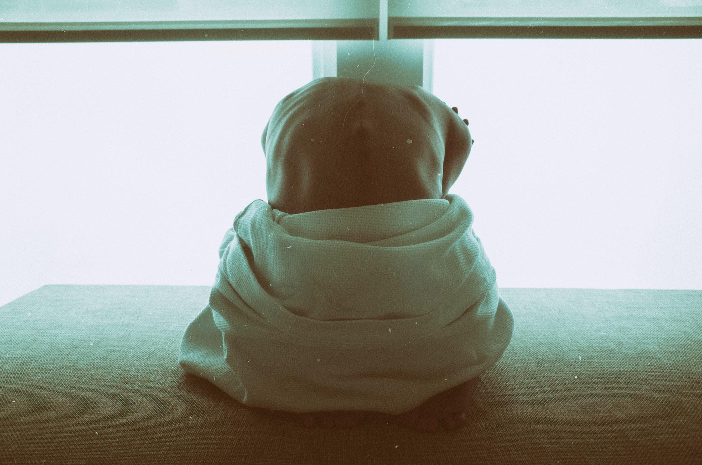 背中を丸めて座っている上半身裸の人