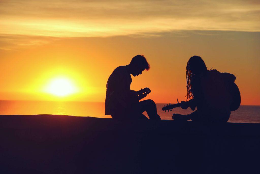 夕日バックに音楽を奏でる男女