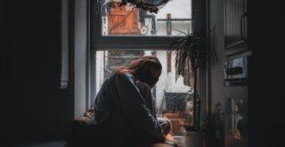 窓際で膝を抱えている女性