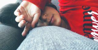 手を額に当てて寝ている人