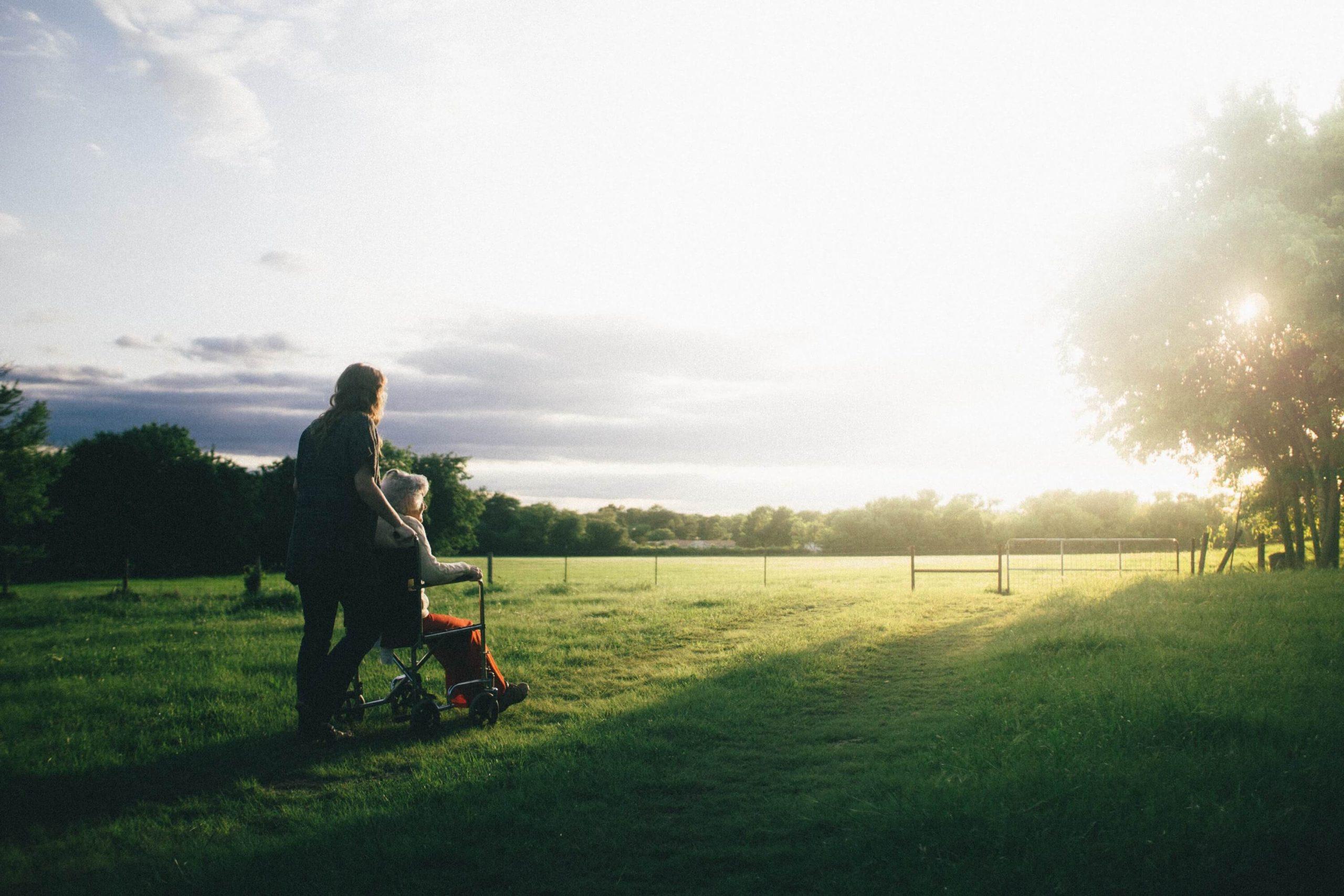 車椅子と介護者の夕日