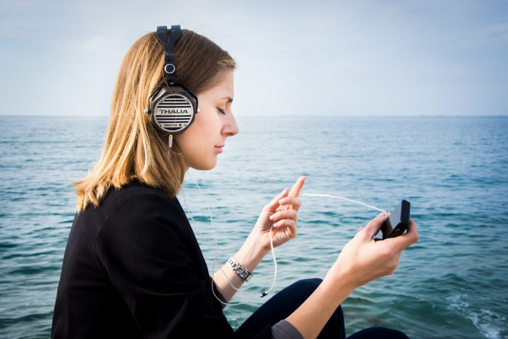 A woman practicing mindfulness while listening to music by the beach.