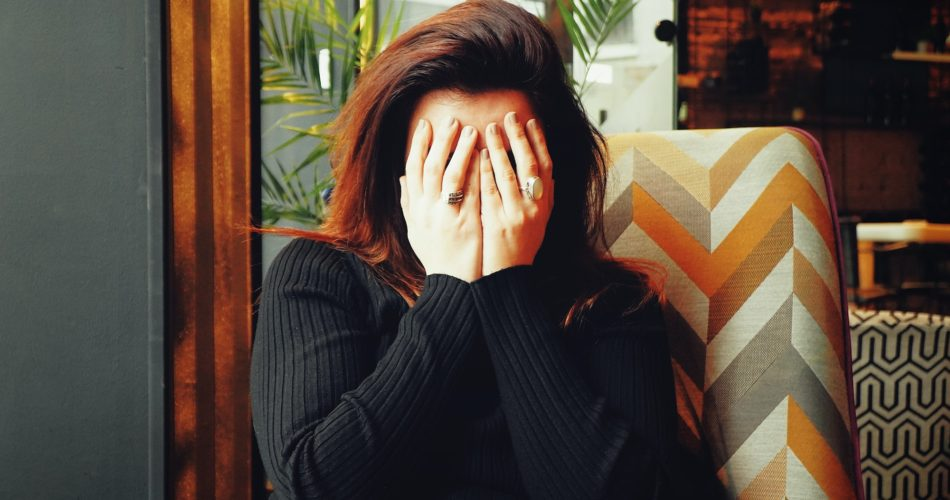 A woman covering her face with her hands