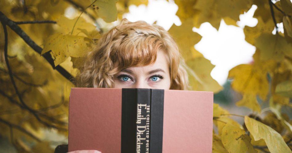 A woman hiding half her face behind a book