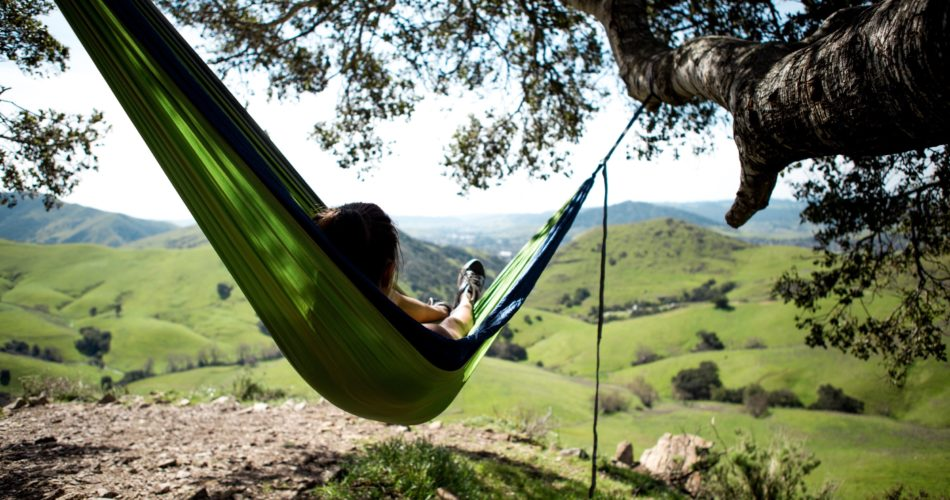 A woman laying on a hammock in nature